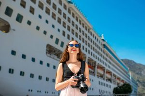 Woman holding camera in front of cruise ship